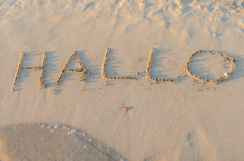 Geschreven woorden Hallo op zand van strand royalty-vrije stock fotografie