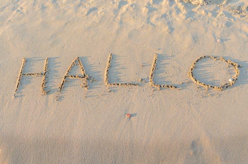 Geschreven woorden Hallo op zand van strand stock foto