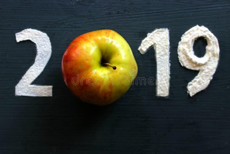 2019 geschrieben in Mehl auf einen schwarzen hölzernen Hintergrund, reifes Apple als Symbol der gesunder Ernährung lizenzfreies stockfoto