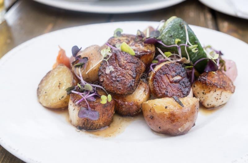 Geschwärzte Kamm-Muscheln gedient mit gekochten Kartoffeln und Zucchini stockfotos