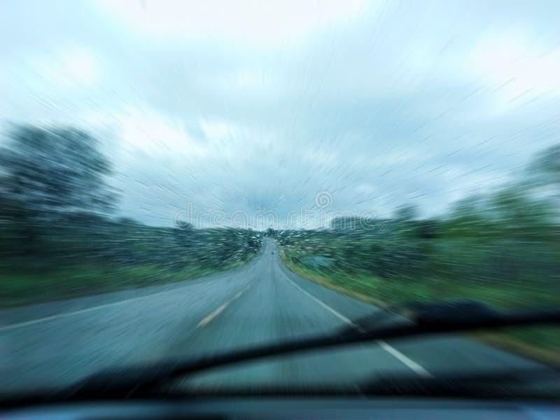 Geschwindigkeit und Regen: Regnen Sie Tropfen gegen das Glas des Autos auf einer Landstraße mit Bewegungsunschärfe stockbild
