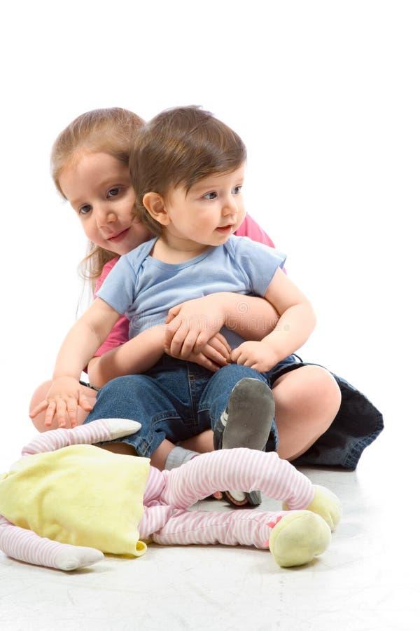 Geschwister - Bruder und Schwester auf Fußboden mit Puppe lizenzfreie stockbilder