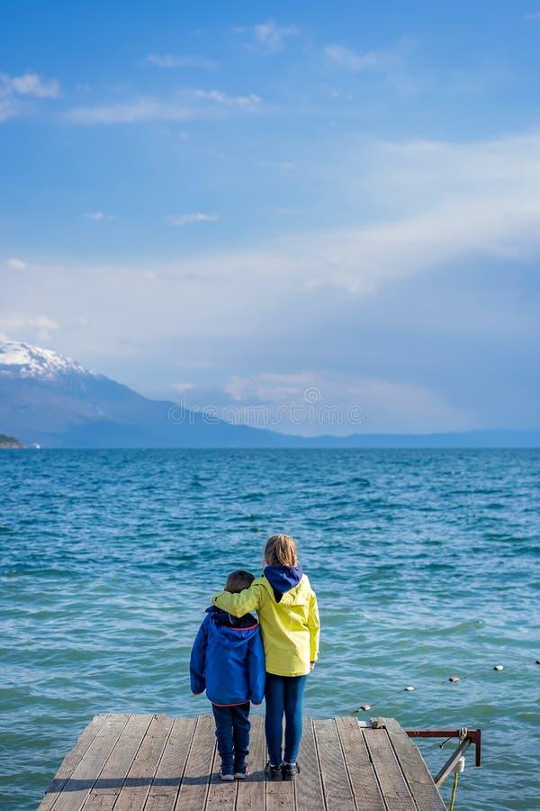 Geschwister, die auf einem hölzernen Pier stehen lizenzfreies stockfoto