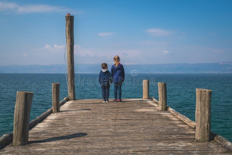 Geschwister, die auf einem hölzernen Pier stehen stockfotos