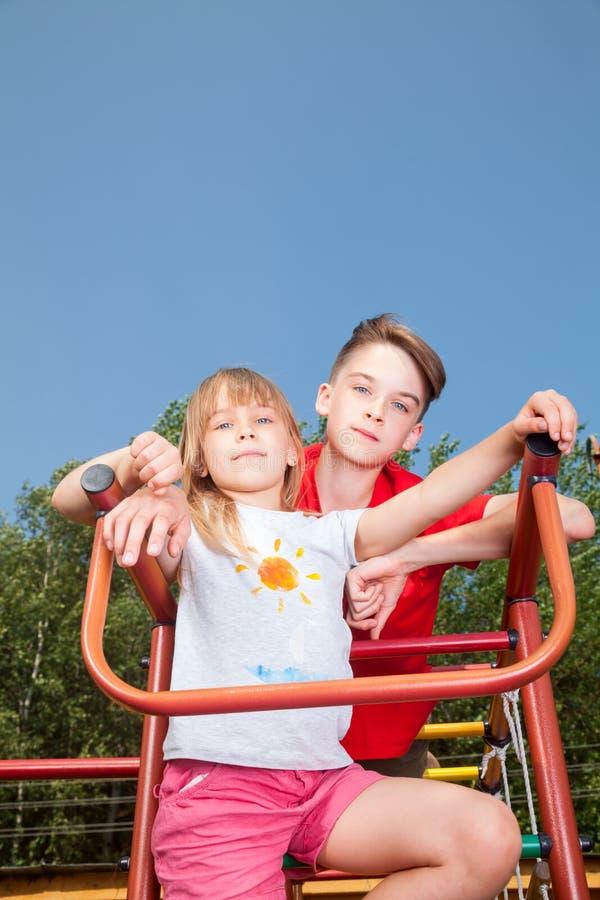 Geschwister, die auf einer Dschungelturnhalle aufwerfen lizenzfreies stockfoto