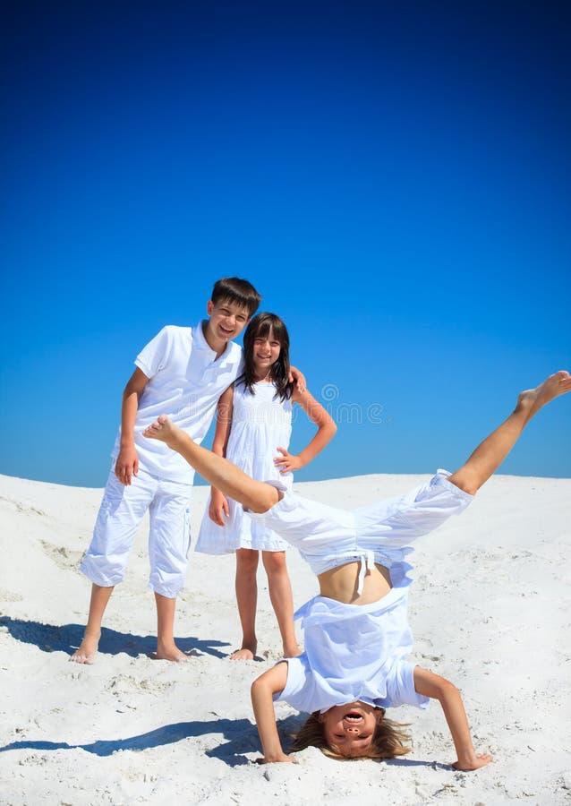 Geschwister, die auf weißem Strand spielen stockfotografie