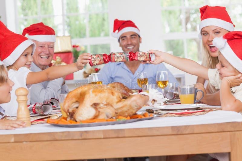 Geschwister, die einen Weihnachtscracker ziehen stockbilder