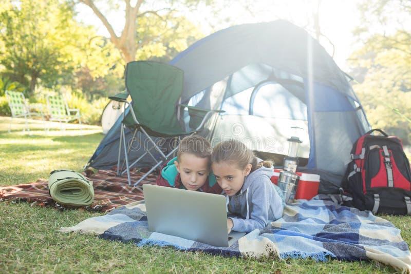 Geschwister, die Laptop außerhalb des Zeltes verwenden stockfoto