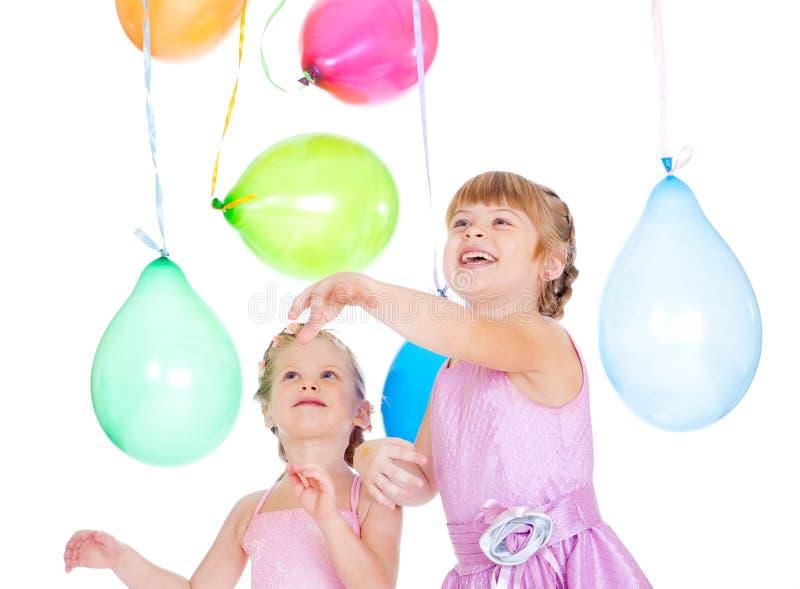 Geschwister, die mit Ballonen spielen lizenzfreie stockfotografie