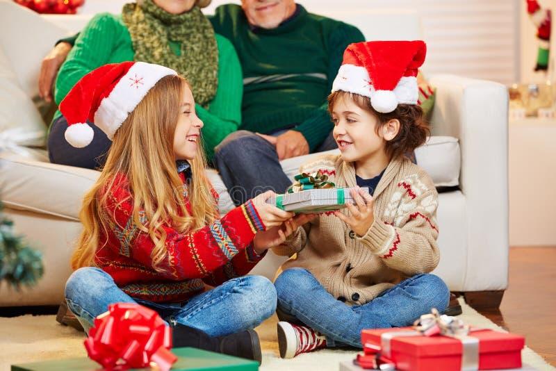 Geschwister, die miteinander Geschenke am Weihnachten geben stockbild