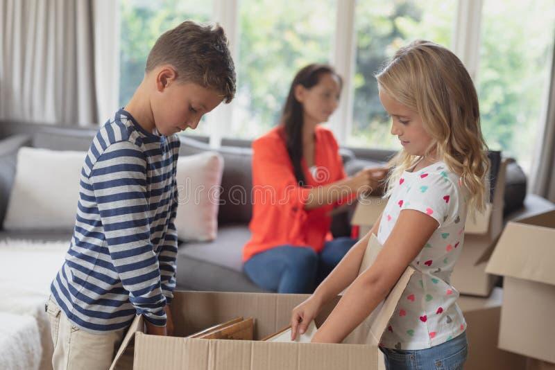Geschwister, die Pappschachtel im Wohnzimmer auspacken stockbilder