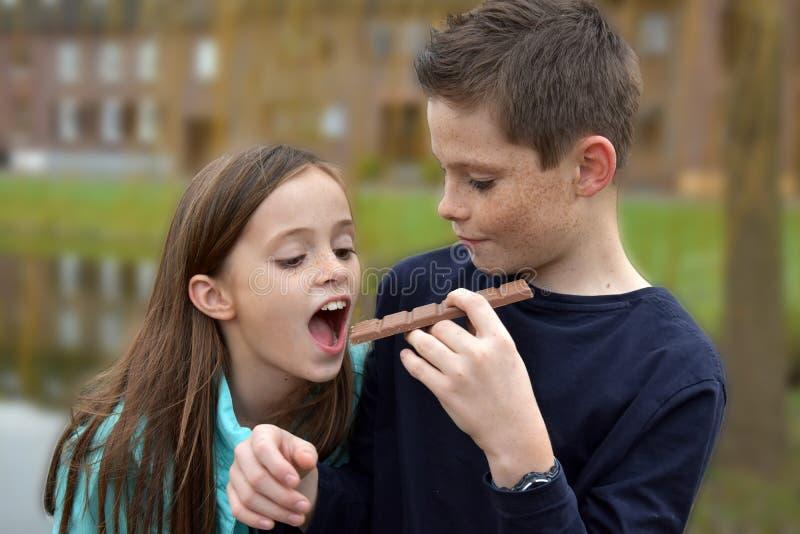 Geschwister, die Schokolade essen stockbilder