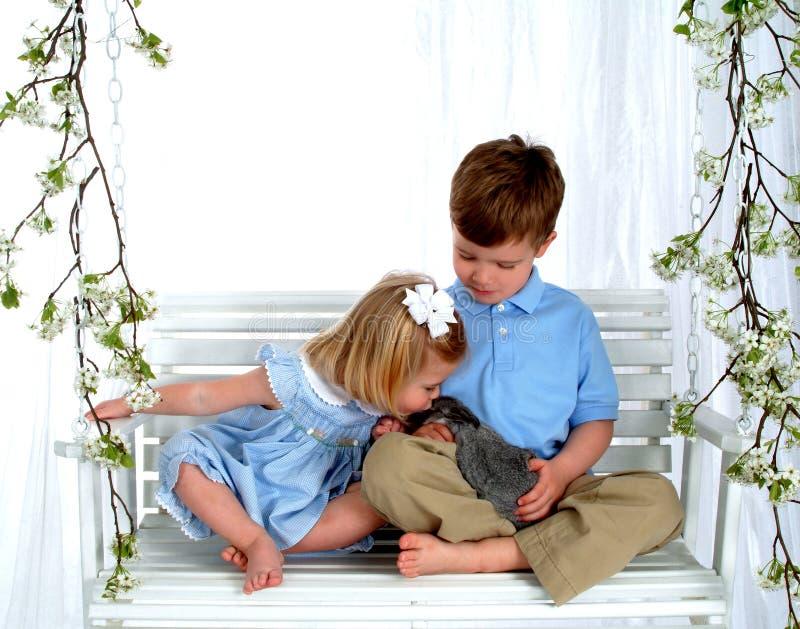 Geschwister und Häschen auf Schwingen stockfotos