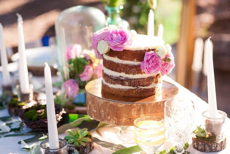 Geschwollene Hochzeitstorte mit Blumen stockfotografie