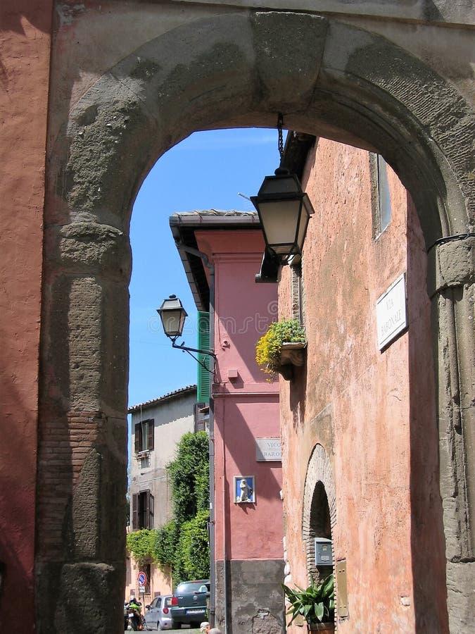 Gesehen durch eine Stadttür zum Bogen von farbigen Häusern eines kleinen Dorfs des Lazios in Italien lizenzfreies stockbild