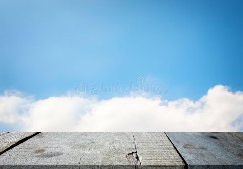Geselecteerde nadruk lege grijze houten lijst en blauw hemeltextuur of w stock foto