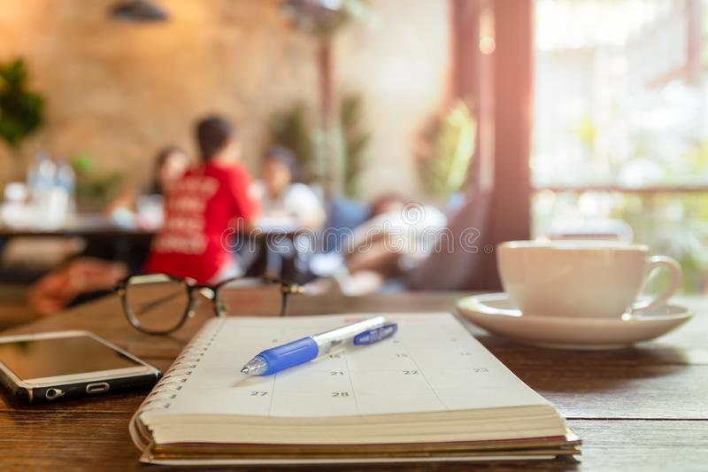 Geselecteerde nadrukpen op kalenderboek met kop van koffie en celtelefoon royalty-vrije stock afbeelding