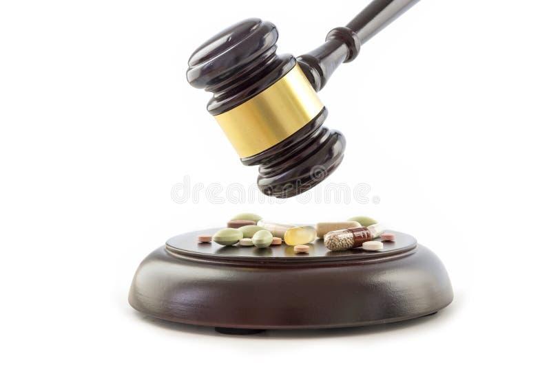 Gesetzeshammer und -drogen, Tabletten und Pillen auf dem hölzernen soliden Block lizenzfreie stockfotografie