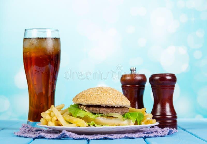 Gesetzter Hamburger, Pommes-Frites und Glas des Schnellimbisses Kolabaum stockfoto