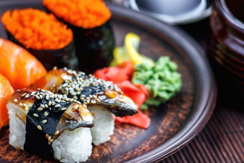 Gesetzter Sashimi der Sushi und Sushirollen dienten auf dunkler Platte Bild des japanischen Lebensmittels auf dunklem Hintergrund stockbild