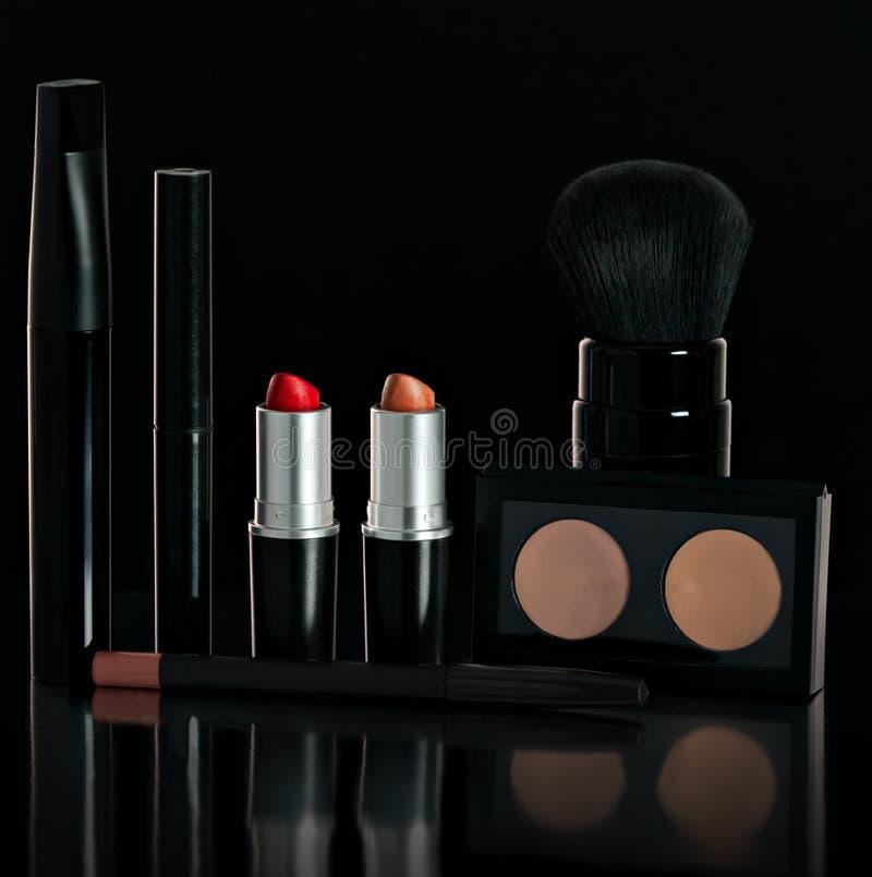 Gesetztes schwarzes Make-up Lippenstift, Wimperntusche, Pulver, Bürste, Bleistift Auf einem schwarzen Hintergrund stockfotos