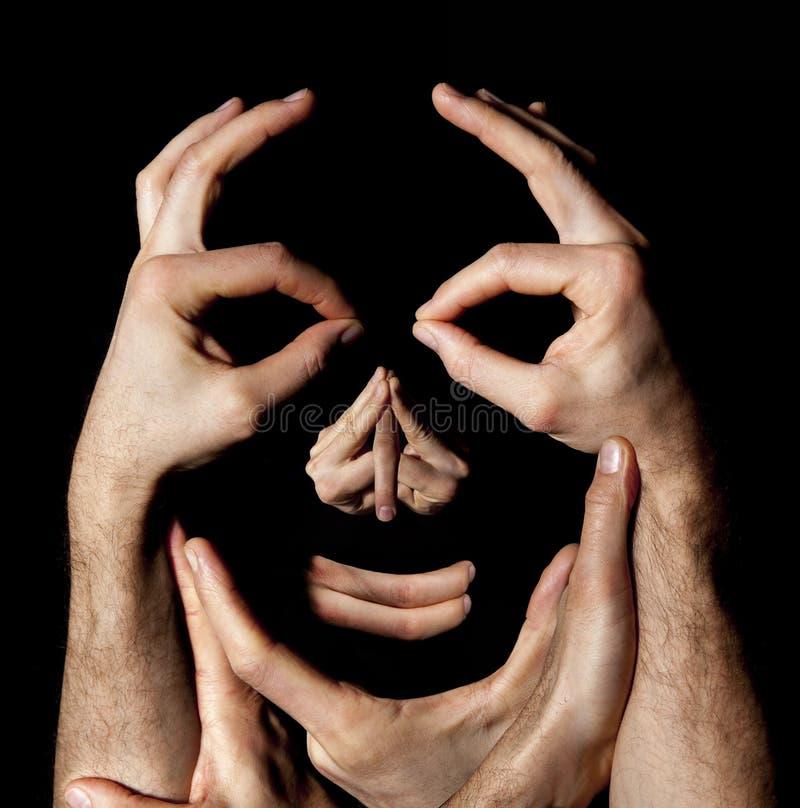 Gesicht übergibt Konzept Grundstückmanipulationsillusion Schwarzer Hintergrund stockfotografie