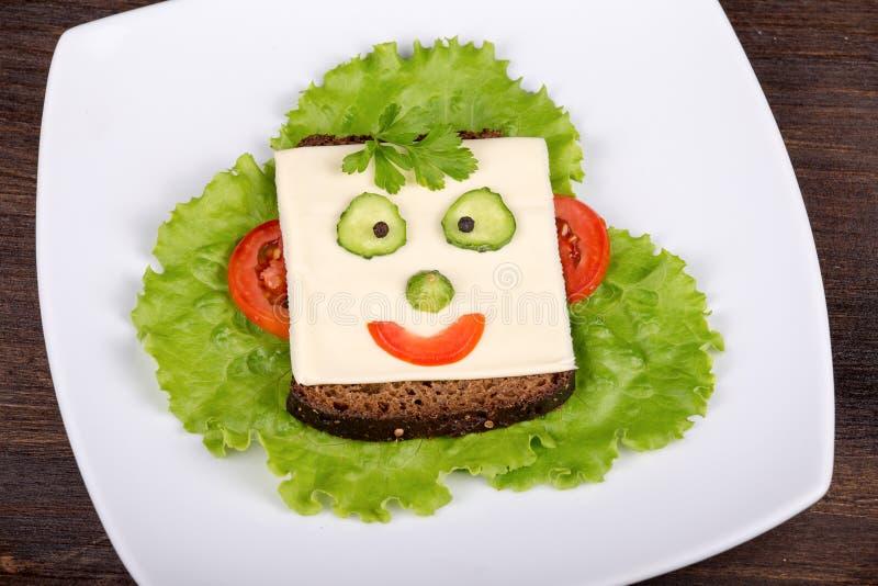 Gesicht auf dem Brot, gemacht vom Käse, vom Kopfsalat, von der Tomate, von der Gurke und vom Pfeffer. lizenzfreies stockbild