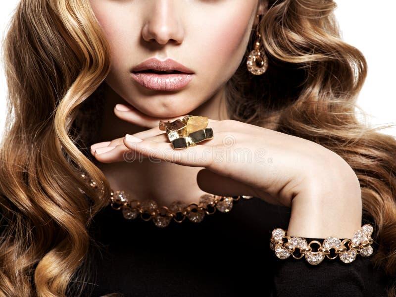 Gesicht der Frau mit langem Haar- und Goldschmuck lizenzfreies stockfoto
