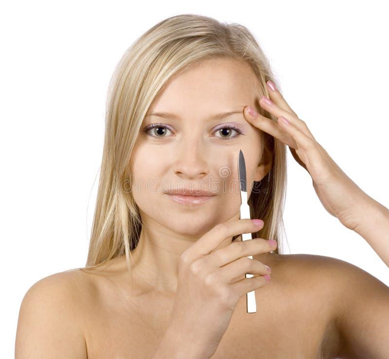 Gesicht der jungen blonden Frau + des Skalpells in ihrer Hand stockbild