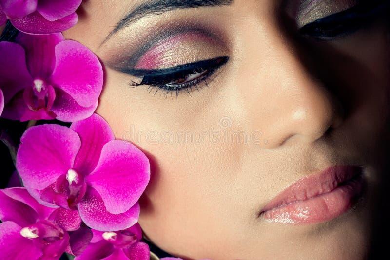 Gesicht der schönen Frau mit Orchideeblumen stockbilder