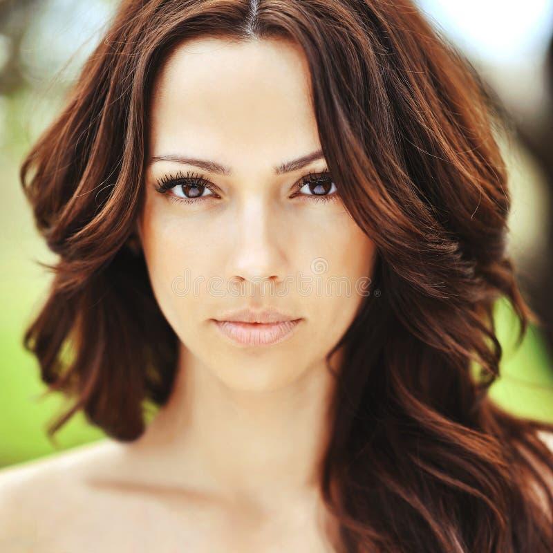 Gesicht der schönen jungen Frau mit dem braunen gelockten Haar stockbilder