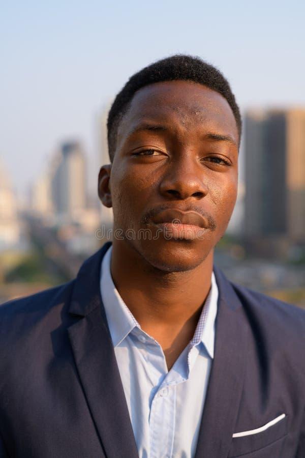 Gesicht des jungen hübschen afrikanischen Geschäftsmannes gegen Ansicht der Stadt stockfotografie