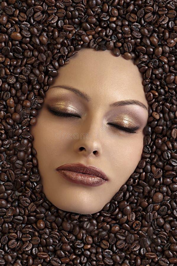 Gesicht des Mädchens untergetaucht in den Kaffeebohnen stockfotografie