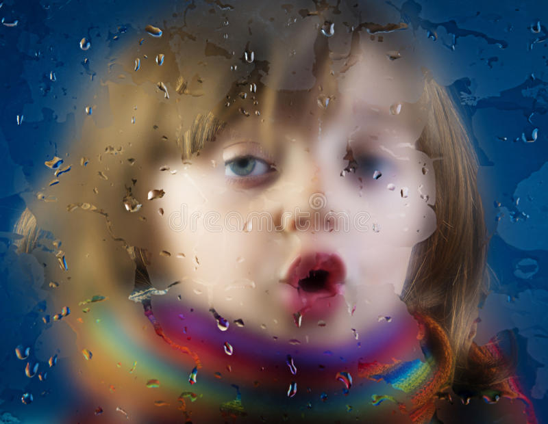 Gesicht eines kleinen Mädchens und des taunassen Fensters stockfotografie