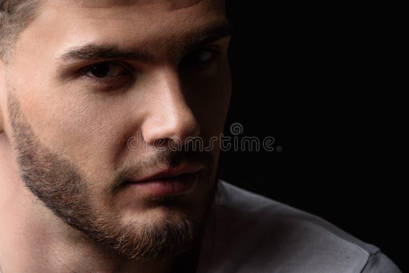 Gesicht eines Mannes, der die Kamera von der Dunkelheit untersucht stockfotografie
