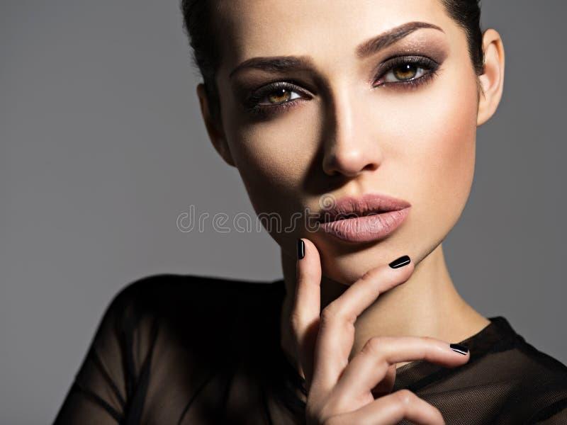 Gesicht eines schönen Mädchens mit rauchigem Augenmake-up stockfotografie