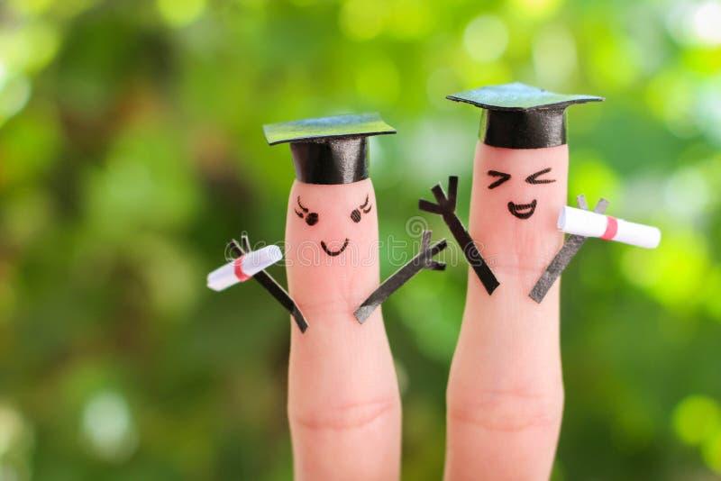 Gesicht gemalt auf den Fingern Studenten, die ihr Diplom nach Staffelung halten stockfotografie