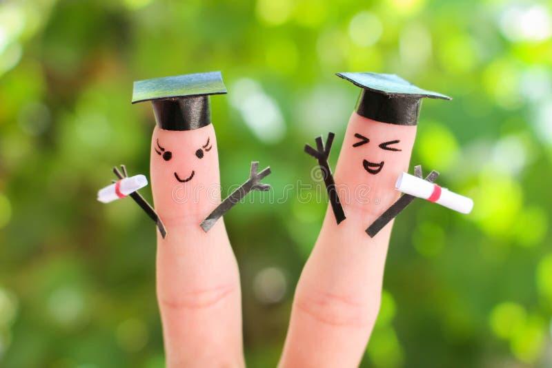 Gesicht gemalt auf den Fingern Studenten, die ihr Diplom nach Staffelung halten stockfoto