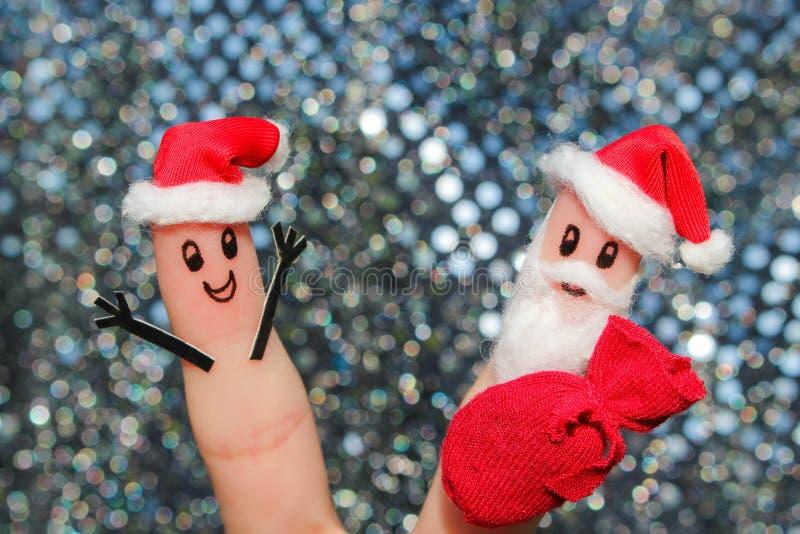 Gesicht gemalt auf den Fingern Weihnachtsmann gibt Geschenke lizenzfreie stockfotografie