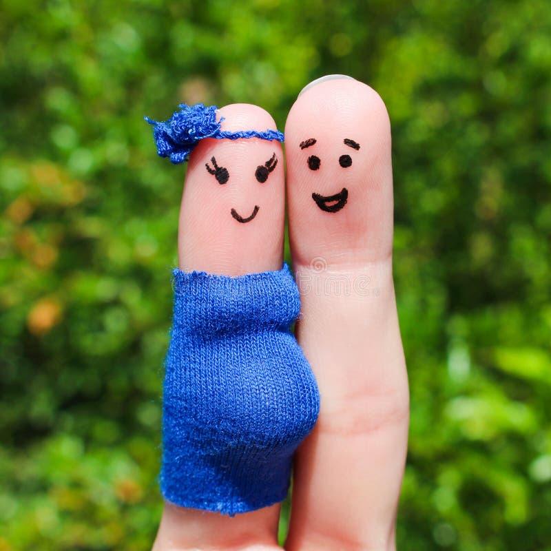 Gesicht gemalt auf Fingern Glückliches Paar, die Frau ist schwanger stockfotografie