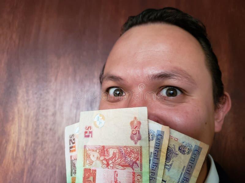 Gesicht mit Gefühlausdruck eines jungen Mannes und der belizischen Banknoten stockbild