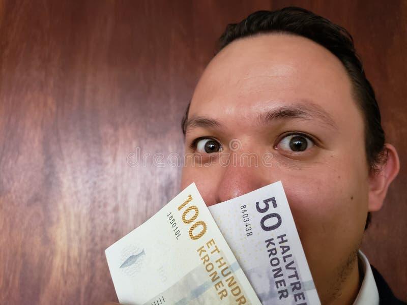 Gesicht mit Gefühlausdruck eines jungen Mannes und der dänischen Banknoten stockfotografie