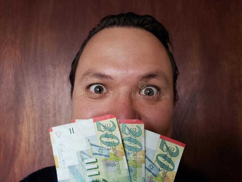 Gesicht mit Gefühlausdruck eines jungen Mannes und der israelischen Banknoten lizenzfreies stockbild