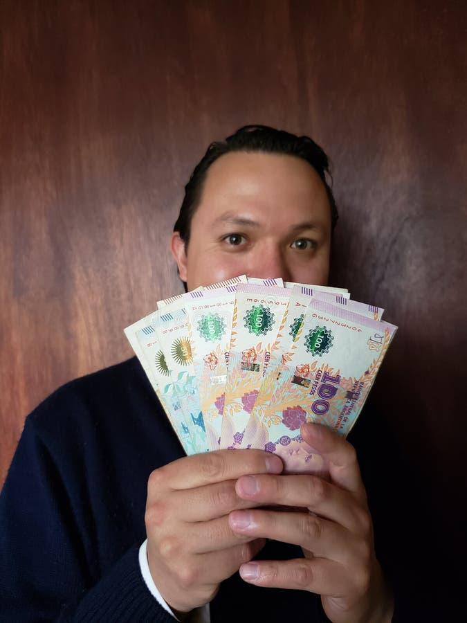 Gesicht mit Gefühlausdruck eines jungen Mannes und des Haltens von Argentinien-Banknoten lizenzfreie stockfotografie