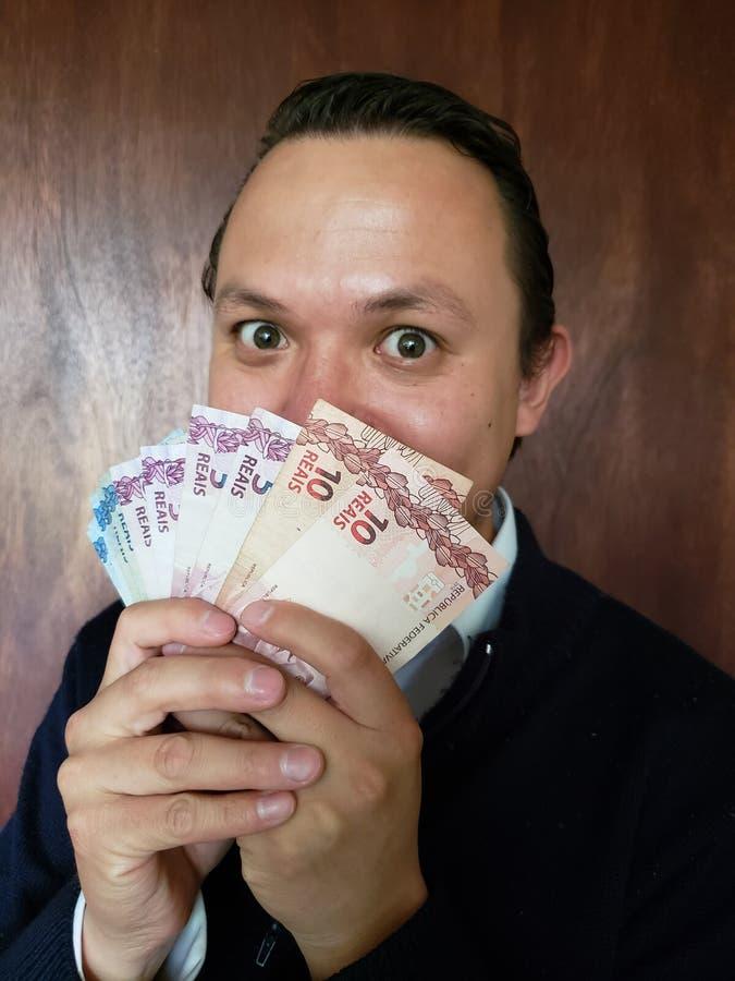 Gesicht mit Gefühlausdruck eines jungen Mannes und des Haltens von brasilianischen Banknoten lizenzfreie stockfotos