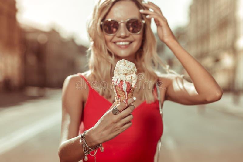 Gesicht-Porträt der Frau das rote Kleid tragend, das Eiscreme in den Händen hält stockfoto