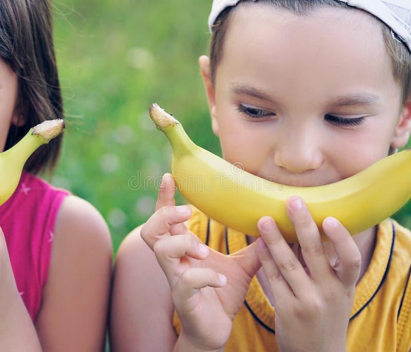 Gesichter eines schönen jungen kaukasischen Mädchens und des Jungen mit Banane lächeln auf Naturhintergrund stockfotografie