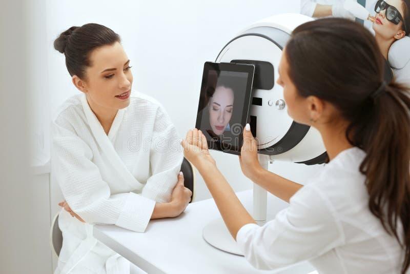 Gesichts-Haut analysieren Cosmetologist-Analyzing Woman Facial-Haut lizenzfreie stockfotos