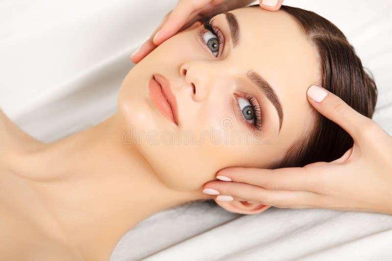 Gesichts-Massage. Nahaufnahme einer jungen Frau, die Badekur erhält. lizenzfreies stockfoto