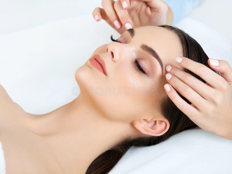 Gesichts-Massage. Nahaufnahme einer jungen Frau, die Badekur erhält. stockbild